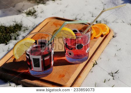 A Pink Beverage In Small Glass On The Wooden Board In Snow For Chilling. Summer Times.