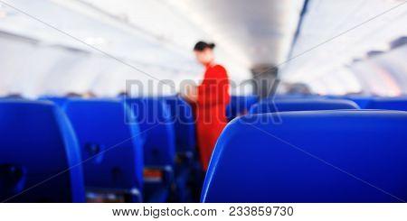 Passenger Seat In Airplane, Interior Of Airplane And Stewardess Background. Stewardess Renders Servi