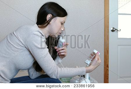 Use Nebulizer And Inhaler For The Treatment. Young Woman Inhaling Through Inhaler Mask Looks At A Vi