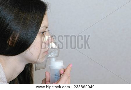 Use Nebulizer And Inhaler For The Treatment. Young Woman Inhaling Through Inhaler Mask. Closeup Side