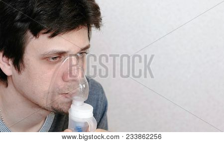 Use Nebulizer And Inhaler For The Treatment. Young Man Inhaling Through Inhaler Mask. Side View.