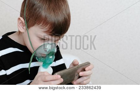 Use Nebulizer And Inhaler For The Treatment. Closeup Boy Inhaling Through Inhaler Mask And Playing T