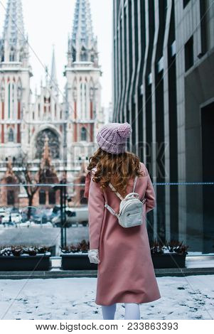 City Tour. Full Length Rear View Of Young Woman In Pink Coat Looking Away While Standing Outdoors.