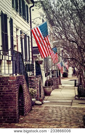 American Flags Waving In The Wind On A Cloudy Day On A Northern Virginia City Street.
