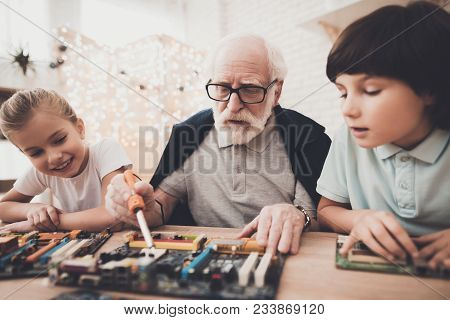 Grandfather, Grandson And Granddaughter At Table At Home. Grandpa Teaches Children How To Braze.
