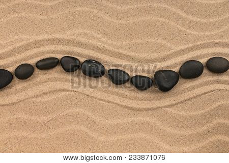 Line Made Of Black Stones Lying Wavy, On Sand Dune. View From Above