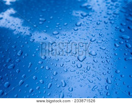 Water Drop On Blue Metal Reflect With Blue Sky And White Cloud For Background In Rainy Season.
