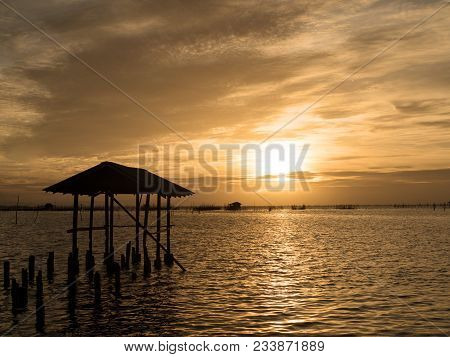 Beautiful Sunset Landscape Orange Golden Sky Above Sea With Silhouette Of Fish Farms.