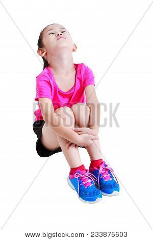 Full Body Of Asian Child In Sportswear Sitting And Exercising Neck, Stretching To Back Of Her Body.