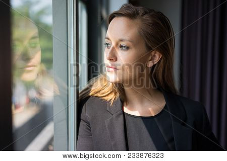 Closeup Portrait Of Pensive Young Beautiful Brown-haired Woman Looking Through Window. Contemplation