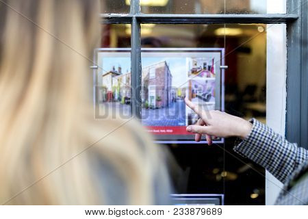 Couple Looking And Pointing At A Property Advert In The Window Of An Estate Agents Or Real Estate Sh