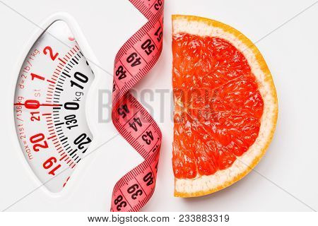 Dieting Healthy Eating Slim Down Concept. Closeup Grapefruit Slice With Measuring Tape On White Weig