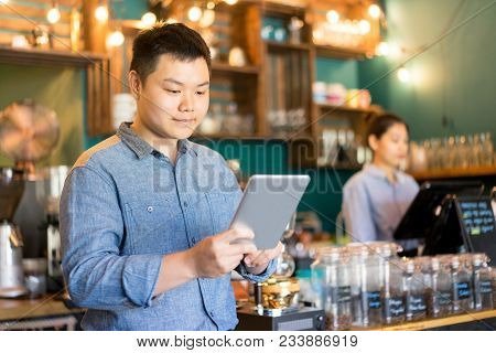 Confident Coffee Shop Manager Using Modern Device At Workplace. Content Ambitious Asian Manager View