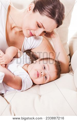 Mom Look On Her Cute Baby Boy On The Bed In Infant Nursery.