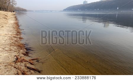 Reflection In The River Of Sky And Shore. Sandy Yellow Bottom Near The Shore In The Foreground. Fog