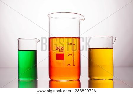 Measuring Beaker With Color Liquids On A White