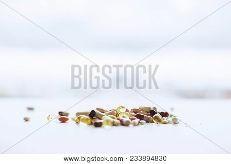 Close up of blurry white desk top with pills and tablets. Medicine and dose concept poster