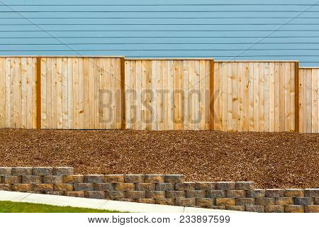 New Garden Wood Fence With House Siding Barkdust Mulch Concrete Retaining Wall Along Exterior Sidewa
