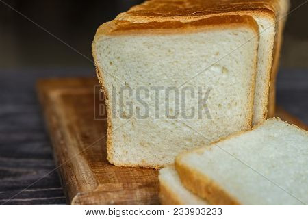 White Bread Sliced With Slices On A Wooden Background Close-up.