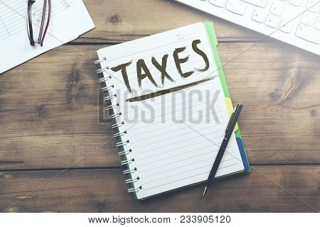 Taxes Text On Notebook With Keyboard On Table