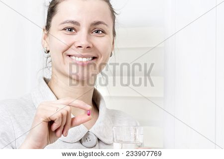 Young Attractive Woman Holds In Her Hand Pill And Glass Of Clean Water. Girl Takes Pills. Healthcare