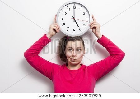 Young Woman Holds Round Clock Over Her Head On White Background. Brunette Girl With Wall Clock In Ha