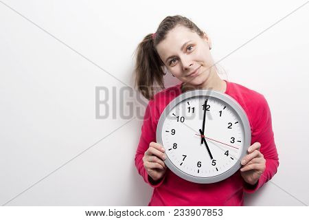 Girl Is Holding Round Clock On White Background. Time Concept. Young Woman With Clock In Hands. Port