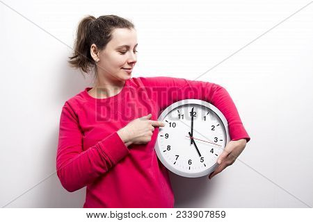Brunette Girl Is Holding Clock And Points To Hands Of Clock On White Background. Concept Of Time. Wa