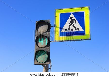 Green Traffic Light With Timer And Pedestrian Crosswalk Stop Sign On Empty Blue Sky Background. City