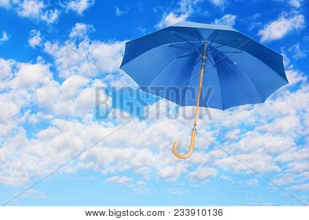 Wind Of Change Concept.blue Umbrella Flies In Sky Against Of White Clouds.mary Poppins Umbrella.