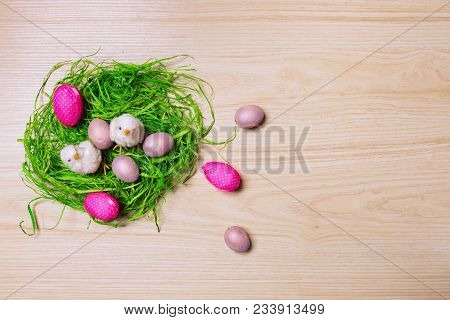 Easter Decorations On Wooden Background With Grass, Rabbit And Eggs. Top View. Pastel Colours.
