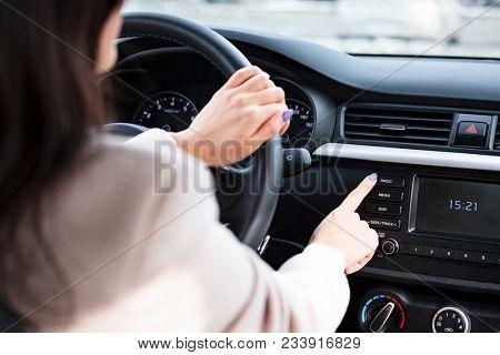 Woman pressing radio button on car's control panel