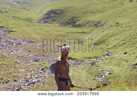 Athletic Naked Man,tourist,stands Half-turned And Looks Into The Camera.he Has Sticks For The Scandi