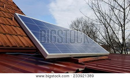 Solar Panel Mounted On Metal Roof With Roof Tiles, Tree Branches And Cloudy Winter Sky In Background