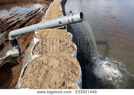 Water Pump Pumping Flood Water Over Tall Sandbox Barriers Through Large Metal Hose On Sunny Winter D
