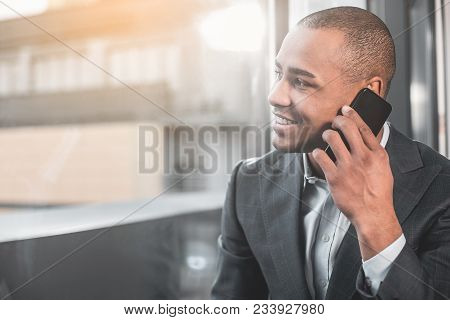 Waist Up African Respectable Guy Talking On Smartphone. He Happily Smiling While Looking To The Side