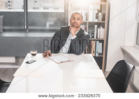 Portrait Of Young Respectable Man Sitting At Cabinet And Touching By Arm To Chin. He Thoughtfully Lo