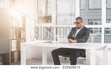 Respectable Man Sitting At Office And Woking With Laptop. Wide Window Is On Background. Copy Space I