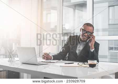 Portrait Of Young African Man Sitting At Office And Talking On Phone. He With Happy Smile Is Looking