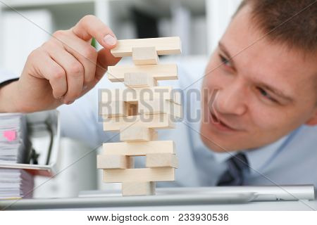 Businessman Plays In Strategy Of Jenga Hand Rearranging Wooden Blocks Involved During Break At Work