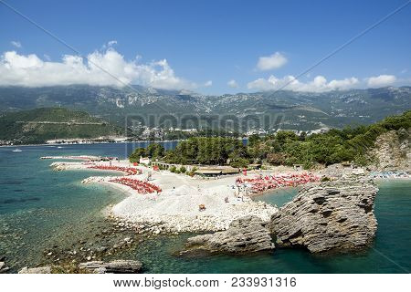 Beautiful Panoramic View Of The Beach With A Large Number Of Bright Red Chaise Lounges, High Mountai