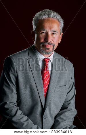 Studio Portrait Of An Older, Handsome, Latino Business Man.  He Is Leaning In Front Of A Dark Red Ba