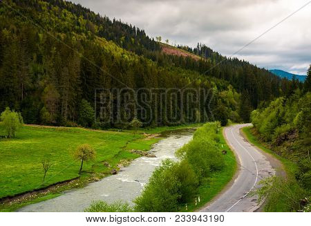 Road Along The River Near The Forest On Hillside. Lovely Springtime Landscape In Mountains On A Clou