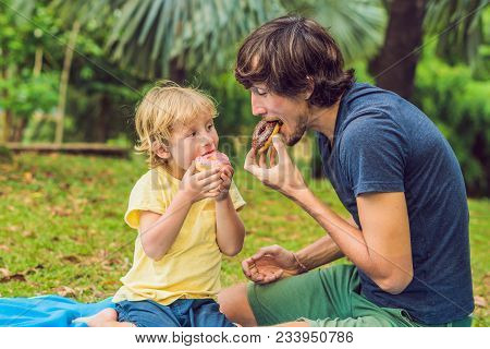 Dad And Son Are Eating A Donut In The Park. Harmful Nutrition In The Family.