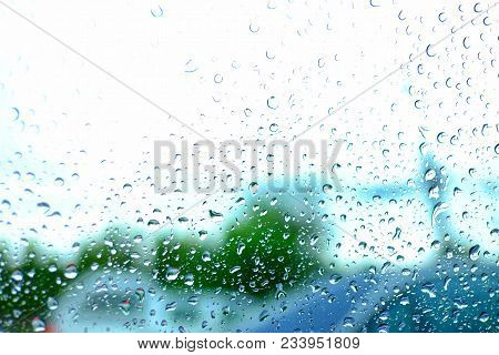 In Selective Focus Of Droplets On Car Mirror With Blurred White Sky And Green Sideways