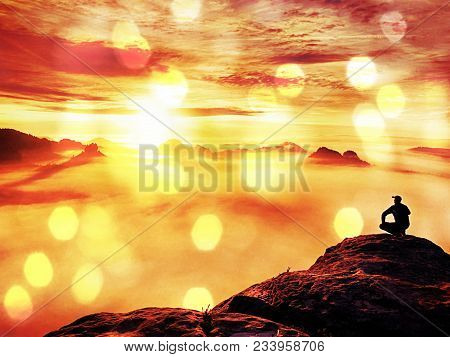 Abstract Effect. Tourist Sit On Peak Of Sandstone Rock And Watching Into Colorful Mist And Fog In  M