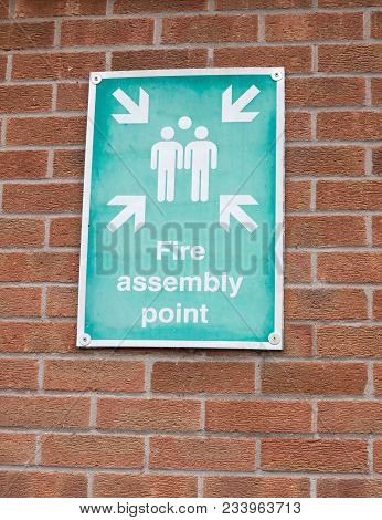 Green And White Fire Assembly Point Sign On Brick Wall