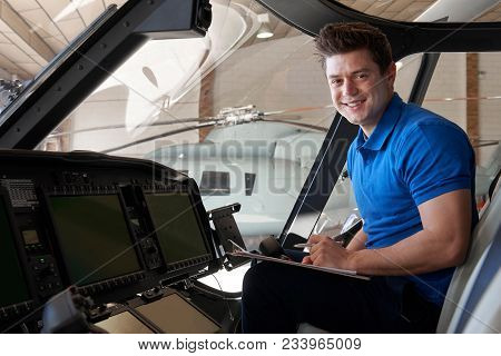 Portrait Of Male Aero Engineer With Clipboard Working In Helicopter Cockpit