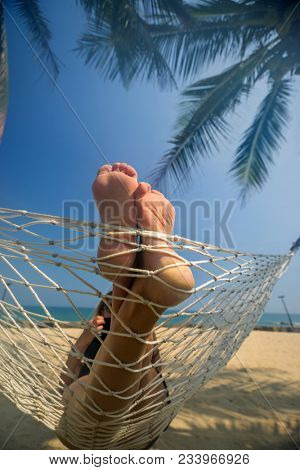 Leisure in summer - Beautiful Tanned legs of sexy women. relax on hammock at sandy tropical beach.