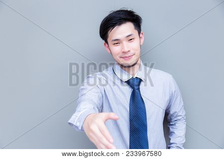Charming Handsome Businessman Is Welcoming A Customer Or Someone By Handshake. Attractive Guy Looks